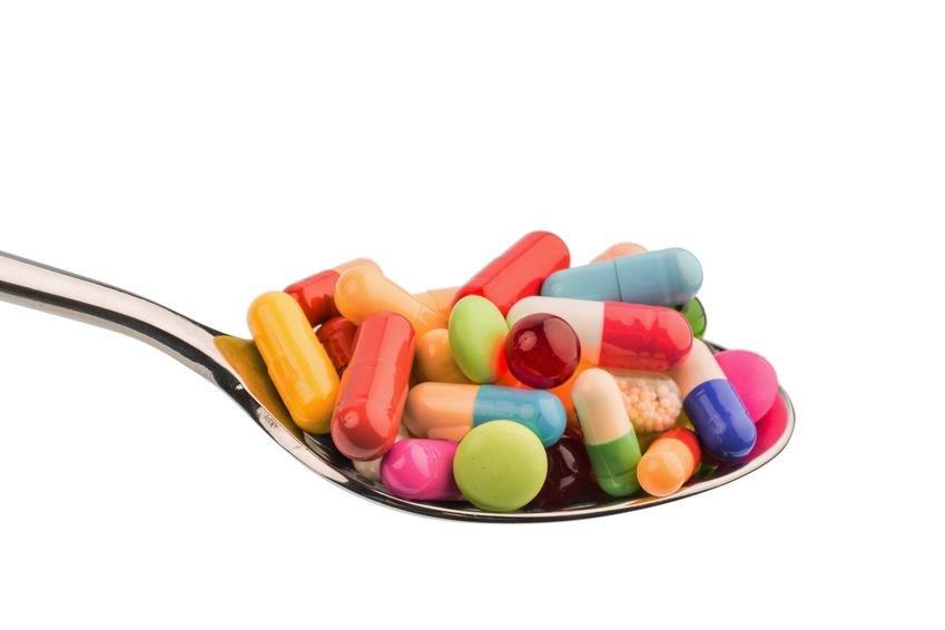 Viele bunte Tabletten auf einem Löffel. Symbolfoto für Tablettensucht und Mißbrauch von Medikamenten.